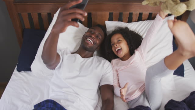 African american father and daughter taking selfie in bed