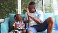 istock African American father give hi five and playing with his little daughter who is learning from digital tablet from home on sofa 1284369058