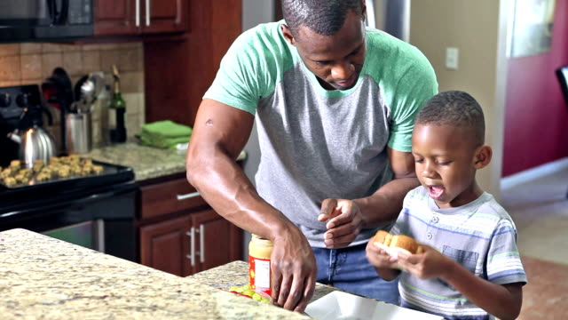 African American father making sandwich for son video