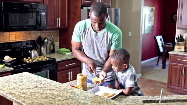 Padre afro americano haciendo sandwich para hijo - vídeo