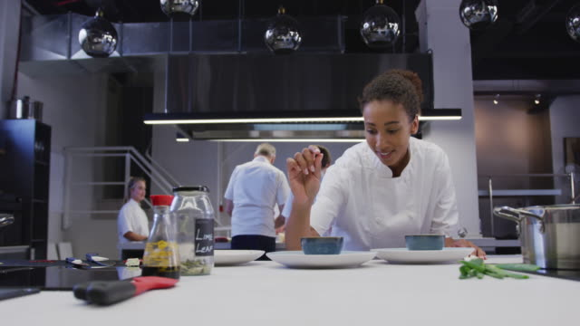 african american female chef wearing chefs whites in a restaurant kitchen seasoning food - busy restaurant kitchen stock videos & royalty-free footage