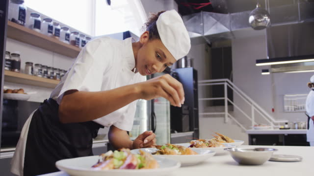 african american female chef wearing chefs whites in a restaurant kitchen, putting food on a plate - busy restaurant kitchen stock videos & royalty-free footage