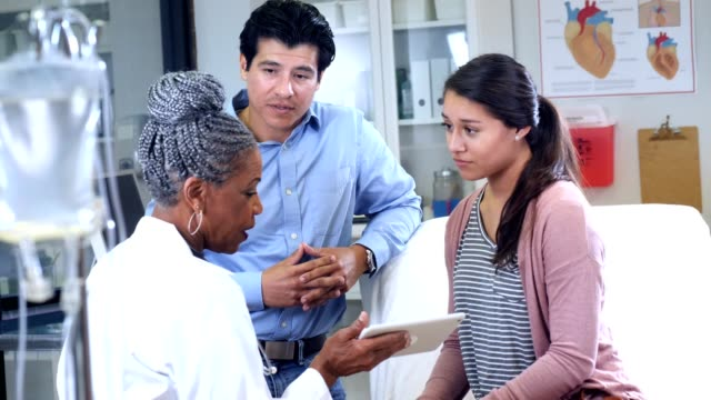 african american female doctor answers questions from a patient's father - ambulatorio medico video stock e b–roll