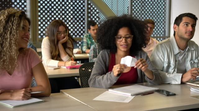 African american female student receiving a note from a friend during class while other students are paying attention