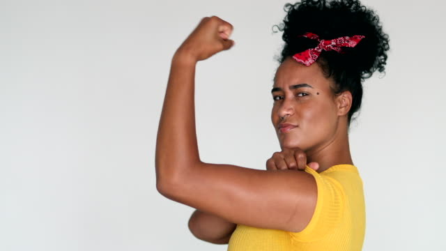 african american feminist woman posing to camera doing we can do it gesture with arm - napinać mięśnie filmów i materiałów b-roll