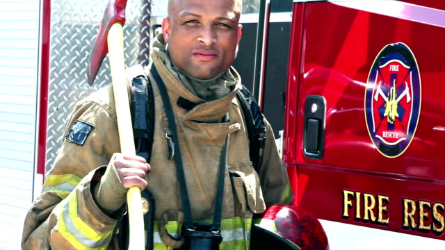 African American fireman standing by truck with axe video