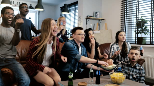 African American friends watching sports on TV. 4K slow motion. Multi ethnic friends celebrate winning together. Emotion video