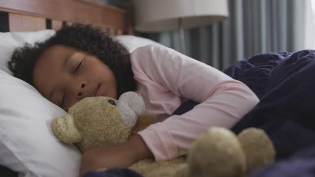 vídeos de stock e filmes b-roll de african american girl sleeping in her bed - teddy bear