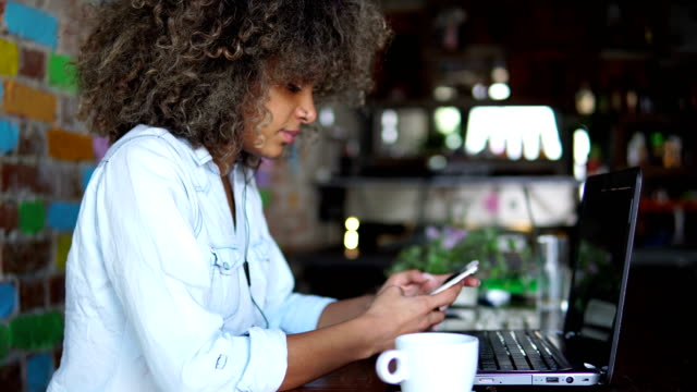 African american girl using smart phone in cafe