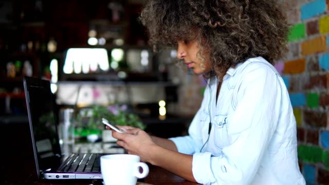 african american girl using smart phone in cafe - pokolenie y filmów i materiałów b-roll