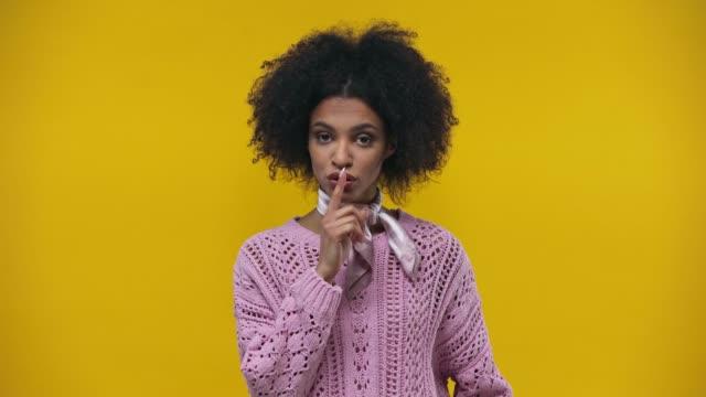 stockvideo's en b-roll-footage met afrikaans amerikaans meisje dat mond ritst die op geel wordt geïsoleerd - stilte