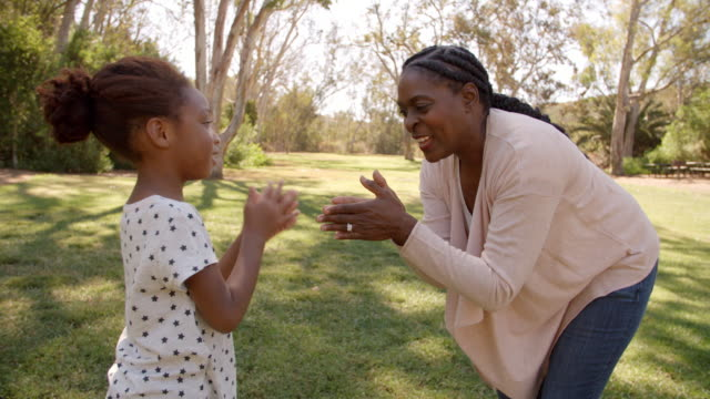 African American grandma playing with granddaughter in park video