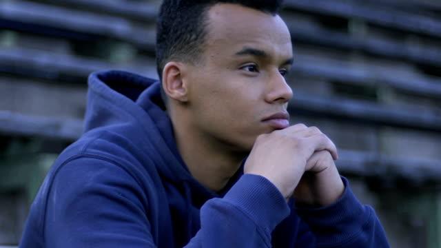 african american kerl sitzt auf der bank, ausschluss aus der schule-sport-team - depression stock-videos und b-roll-filmmaterial