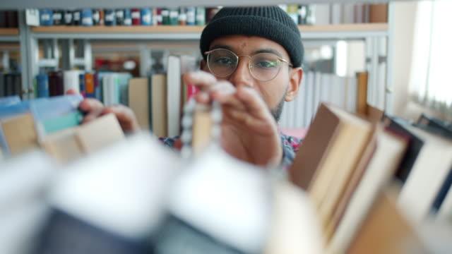 stockvideo's en b-roll-footage met african american guy student op zoek door boeken op planken in bibliotheek - literatuur