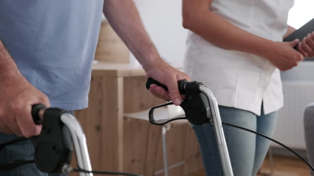 African American healthcare worker helping a senior man with a mobility walker African American healthcare worker helping a senior man with a mobility walker orthopedic equipment stock videos & royalty-free footage