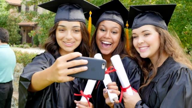 Amigos de Colegio de afroamericanos, hispanos y caucásicos toman autorretratos después de la graduación - vídeo