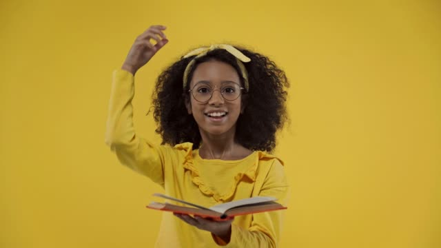 african american kid gesturing and holding book isolated on yellow