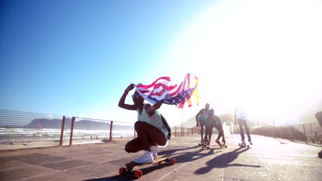 vidéos et rushes de african american longboarder flying un drapeau américain - patriotisme