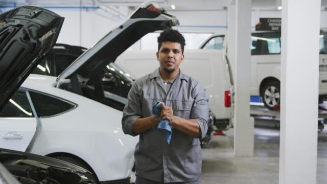 afroamerikansk manlig bilmekaniker rengöring händerna med en trasa och titta på kameran - mekaniker bildbanksvideor och videomaterial från bakom kulisserna