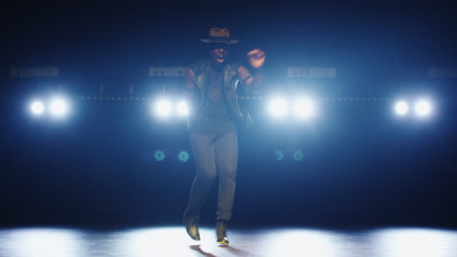 African american male dancer in a hat dancing on a dark stage against the lights. video