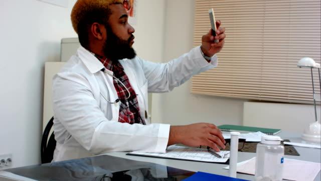 afroamerikanska manliga läkare tar selfie och visar tummen upp - hospital studio bildbanksvideor och videomaterial från bakom kulisserna