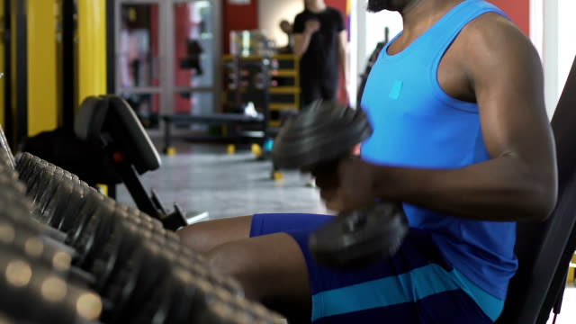 African American male doing alternate dumbbell lift-up, growing biceps, workout video