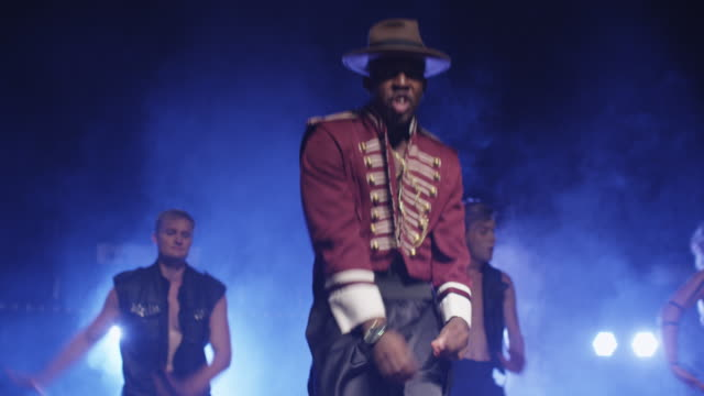african american male in a hat and costume is leading a group of dancers while singing on a dark stage with lights. - hip hop video stock e b–roll