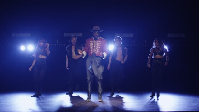vídeos de stock e filmes b-roll de african american male in a hat and costume is leading a group of dancers while singing on a dark stage with lights. - atuação