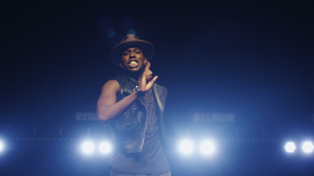 African american male in a hat is singing and dancing on a dark stage. video