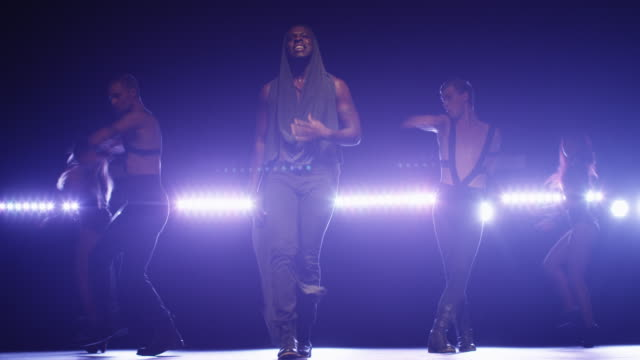 African american male in a hoodie leads a group of dancers while singing on a dark stage with lights. video