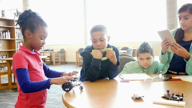 African American male mid-adult teacher supervise as elementary and middle school students work with robot video
