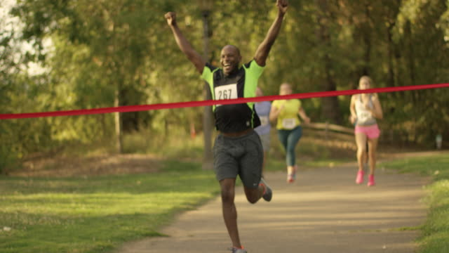 African American male running through a ribbon and finish line during race