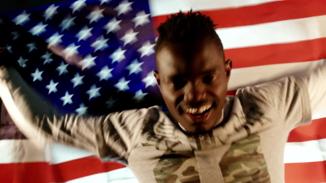 African American male with American flag in hands video