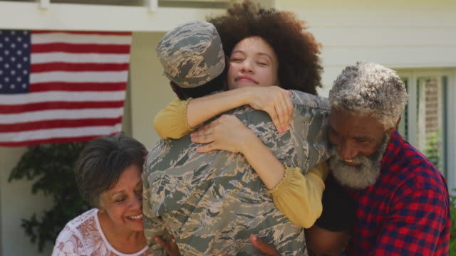 African American man coming back home with his family Multi-generation mixed race family enjoying their time at a garden, welcoming a mixed race man wearing military uniform, returning home, embracing his partner, in slow motion military lifestyle stock videos & royalty-free footage