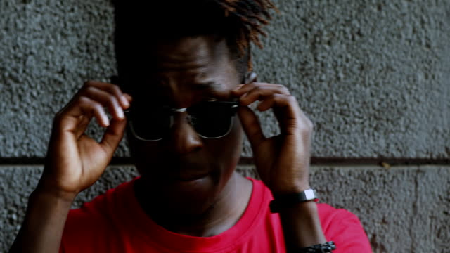 African american man cool guy wear sunglasses against wall closeup African american man cool guy wear sunglasses against wall closeup locs hairstyle stock videos & royalty-free footage