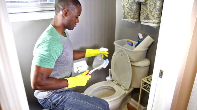 Hombre del afroamericano haciendo las tareas domésticas, limpieza de aseo - vídeo
