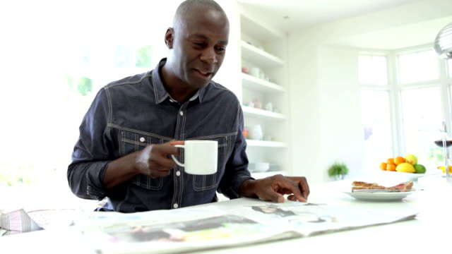 African American Man Eating Breakfast And Reading Newspaper video