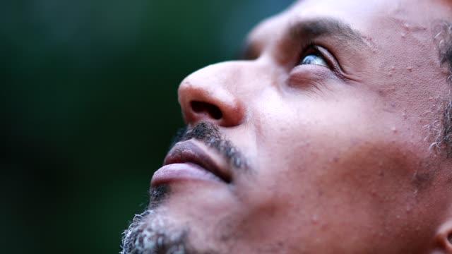 afroamerikanska mannen ansikte slutna ögon känsla andlig överväger och firar livet. svart person som öppnar ögonen mot himlen - krucifix bildbanksvideor och videomaterial från bakom kulisserna