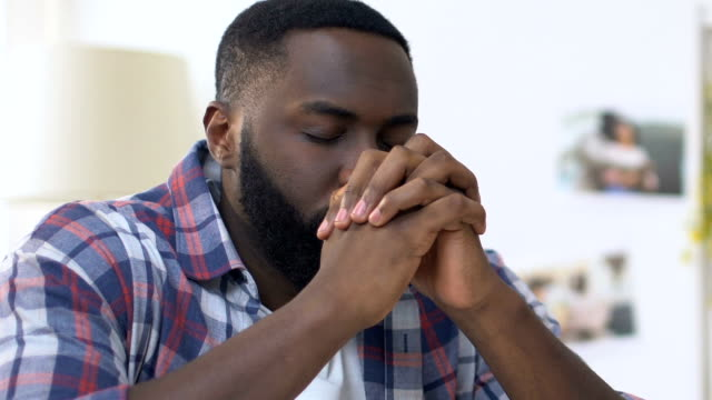 African american man folding hands in prayer, sincere faith in god, religion