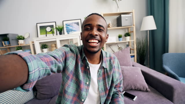African American man having online video call holding smartphone sitting on couch at home