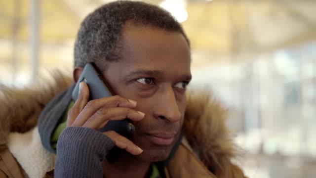 vídeos de stock e filmes b-roll de african american man having phone conversation - esplanada portugal