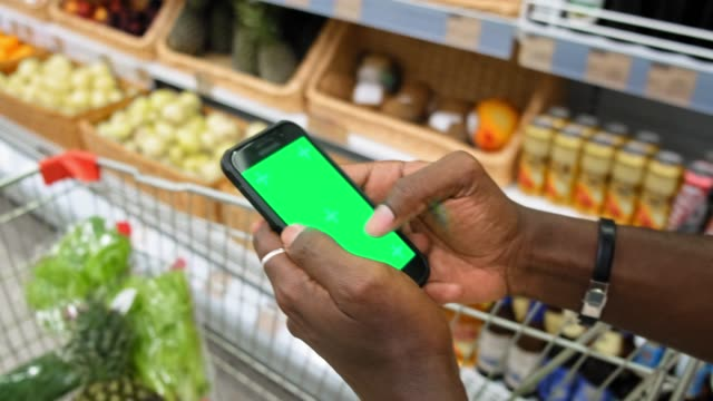 African American man in a supermarket with a green screen smartphone goes along fresh vegetables video