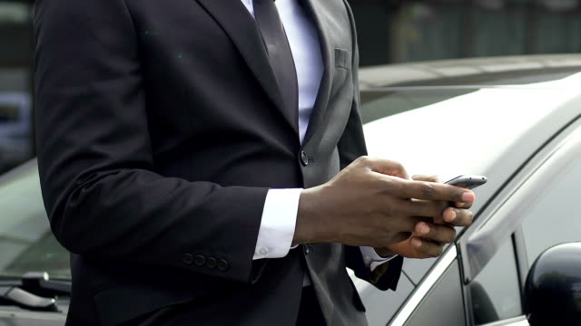 afrikanische amerikanische mann in anzug eingeben nachricht stand in der nähe seines wagens - teurer lebensstil stock-videos und b-roll-filmmaterial