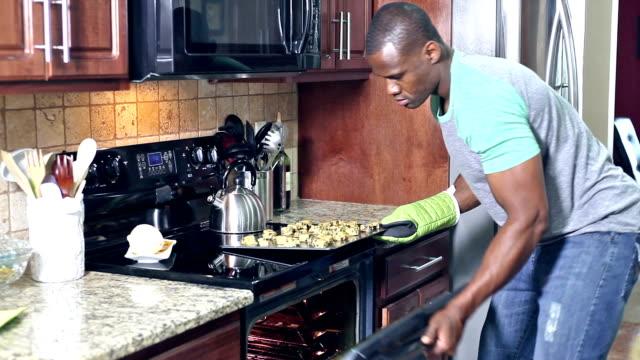 Hombre afroamericano en cocina para hornear galletas - vídeo