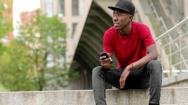 kırmızı t-shirt afro-amerikan erkekte kullanma smartphone yağmur altında - kep şapka stok videoları ve detay görüntü çekimi