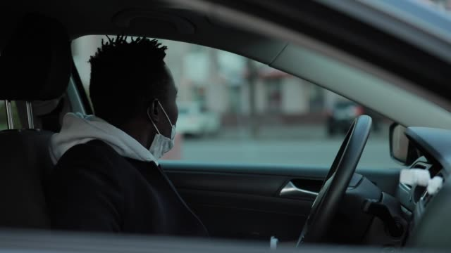 African american man in surgical mask opening window in a car video
