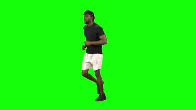 vídeos de stock e filmes b-roll de african american man is running at green screen, chroma key - teeshirt template