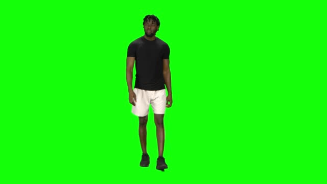 vídeos de stock e filmes b-roll de african american man is walking at green screen, chroma key. front view - teeshirt template