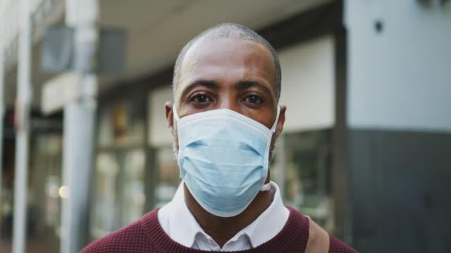 African american man on the go wearing coronavirus covid19 mask