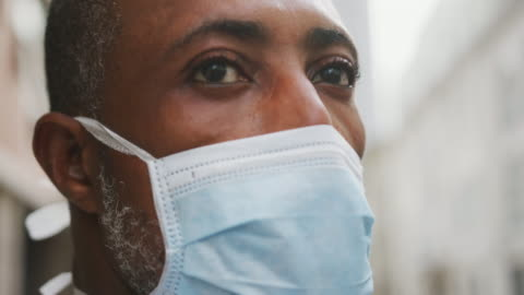 African american man on the go wearing coronavirus covid19 mask African American man out and about in the city streets during the day, wearing a face mask against air pollution and covid19 coronavirus. covid stock videos & royalty-free footage